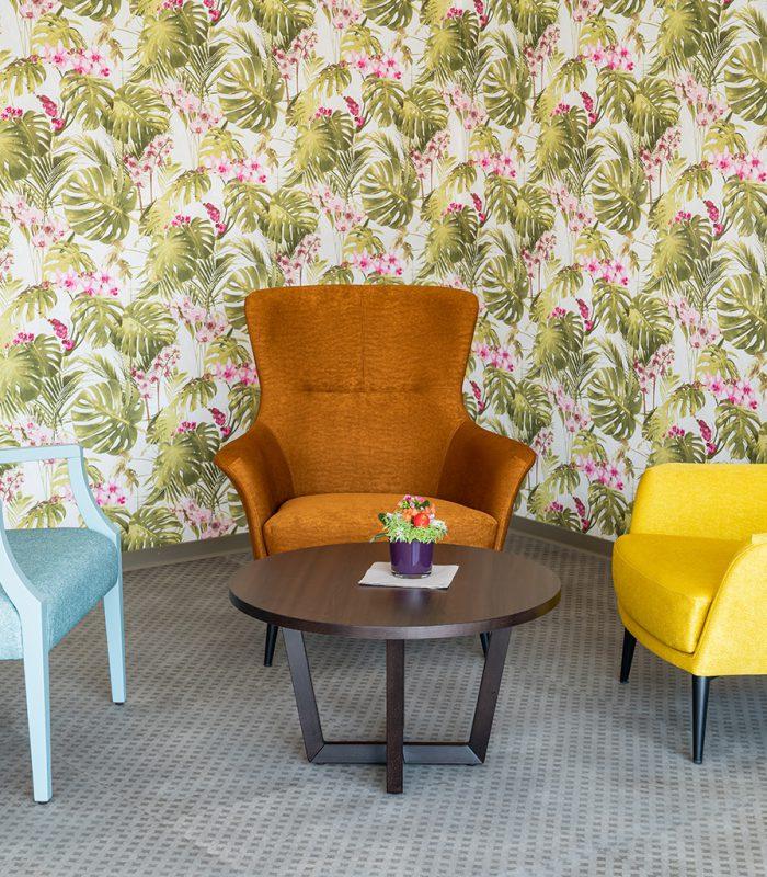 Bunte Sessel in der Aufenhaltsecke mit floraler Tapete in Blumberg
