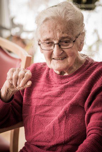 Seniorin im Servicehaus Sonnenhalde mit rotem Pullover