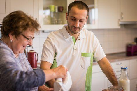 Seniorin mit Altenpfleger beim Kuchen backen