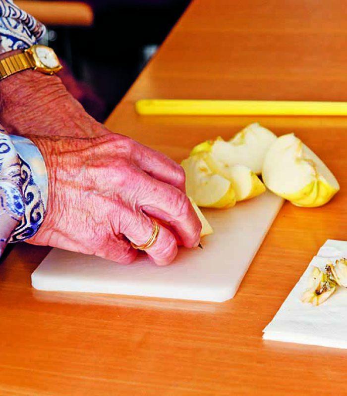 Frau schneidet Äpfel klein